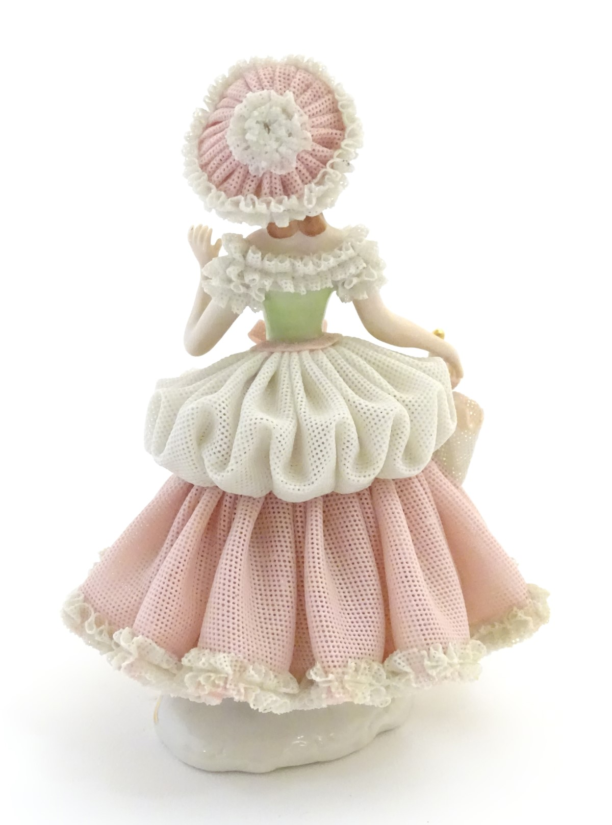 Lot 46 - A Dresden porcelain figure of a lady wearing a porcelain lace dress and hat holding an umbrella.