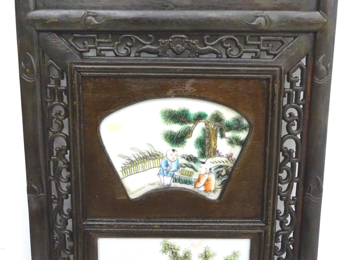 Lot 33 - A Chinese panel with three ceramic tiles in a linear setting,