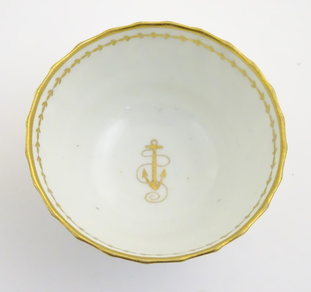 Lot 56 - A 19thC white porcelain tea bowl with ribbed sides and gilt decoration of stylised foliage and