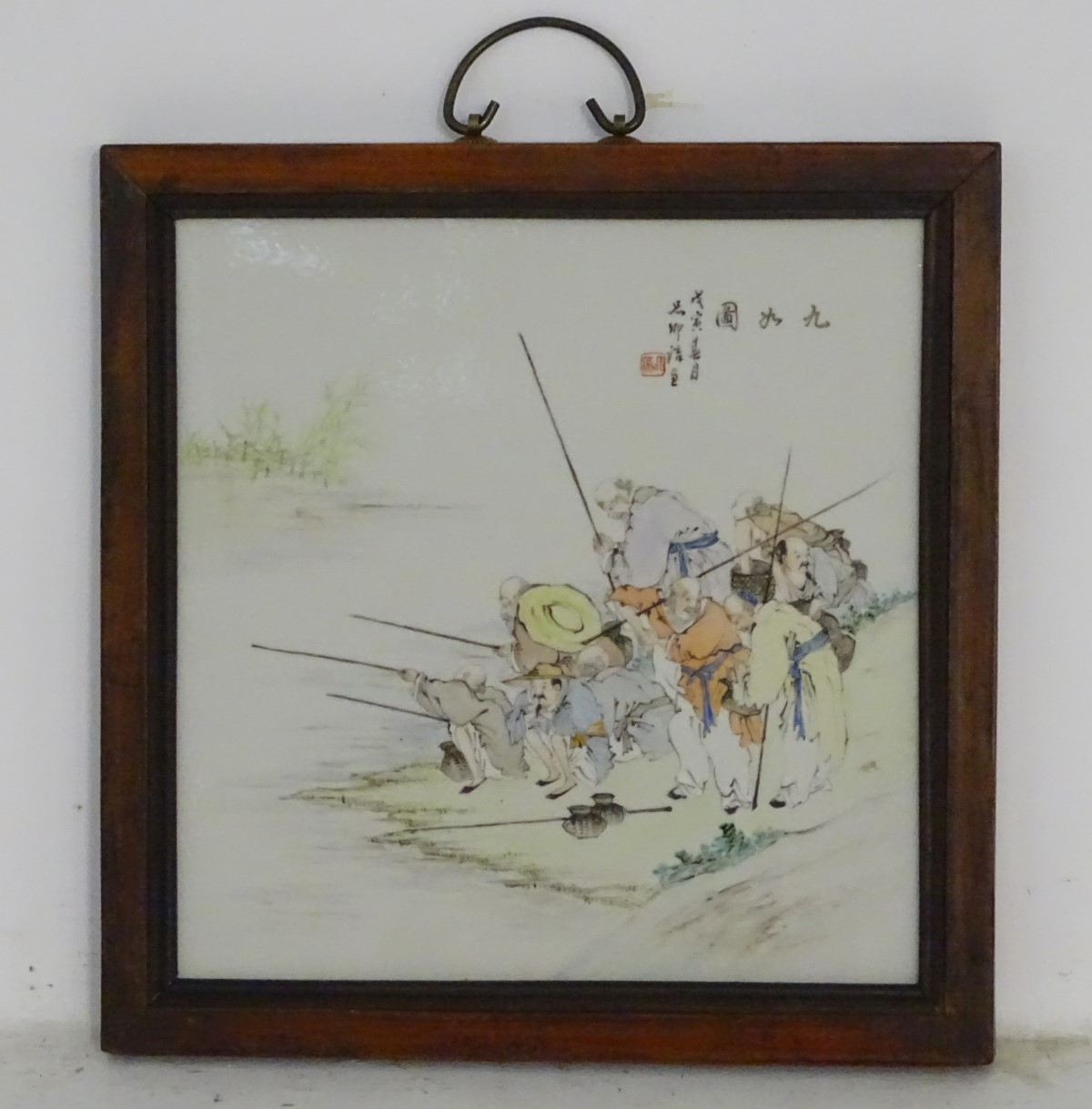 Lot 31 - A 20thC Chinese wooden wall hanging with a porcelain panel depicting elders fishing on the bank of
