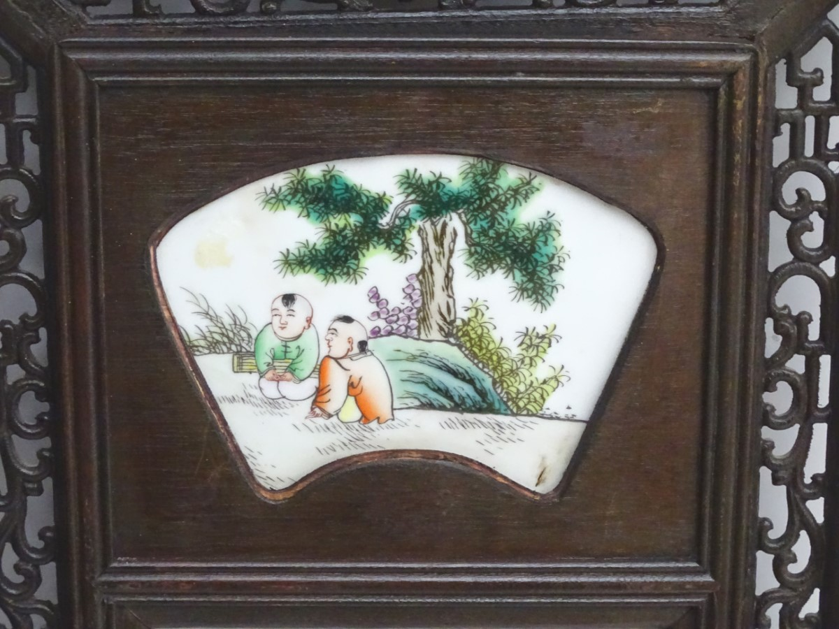 Lot 32 - A Chinese panel with three ceramic tiles in a linear setting,