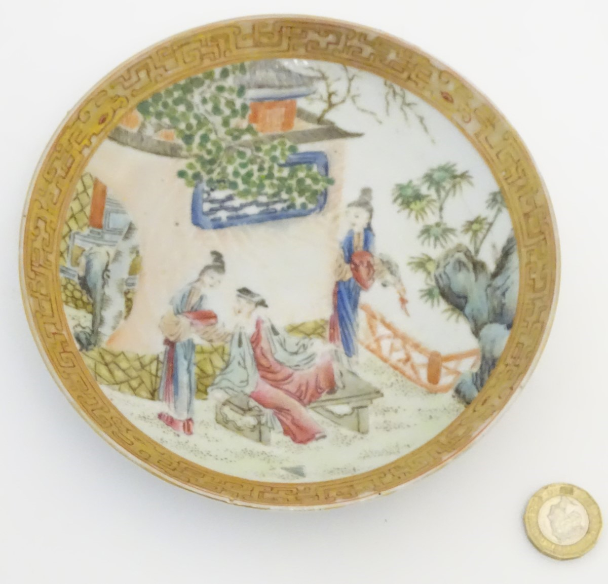 Lot 20 - A small Chinese famille rose plate decorated with figures on a terrace within a landscape with a