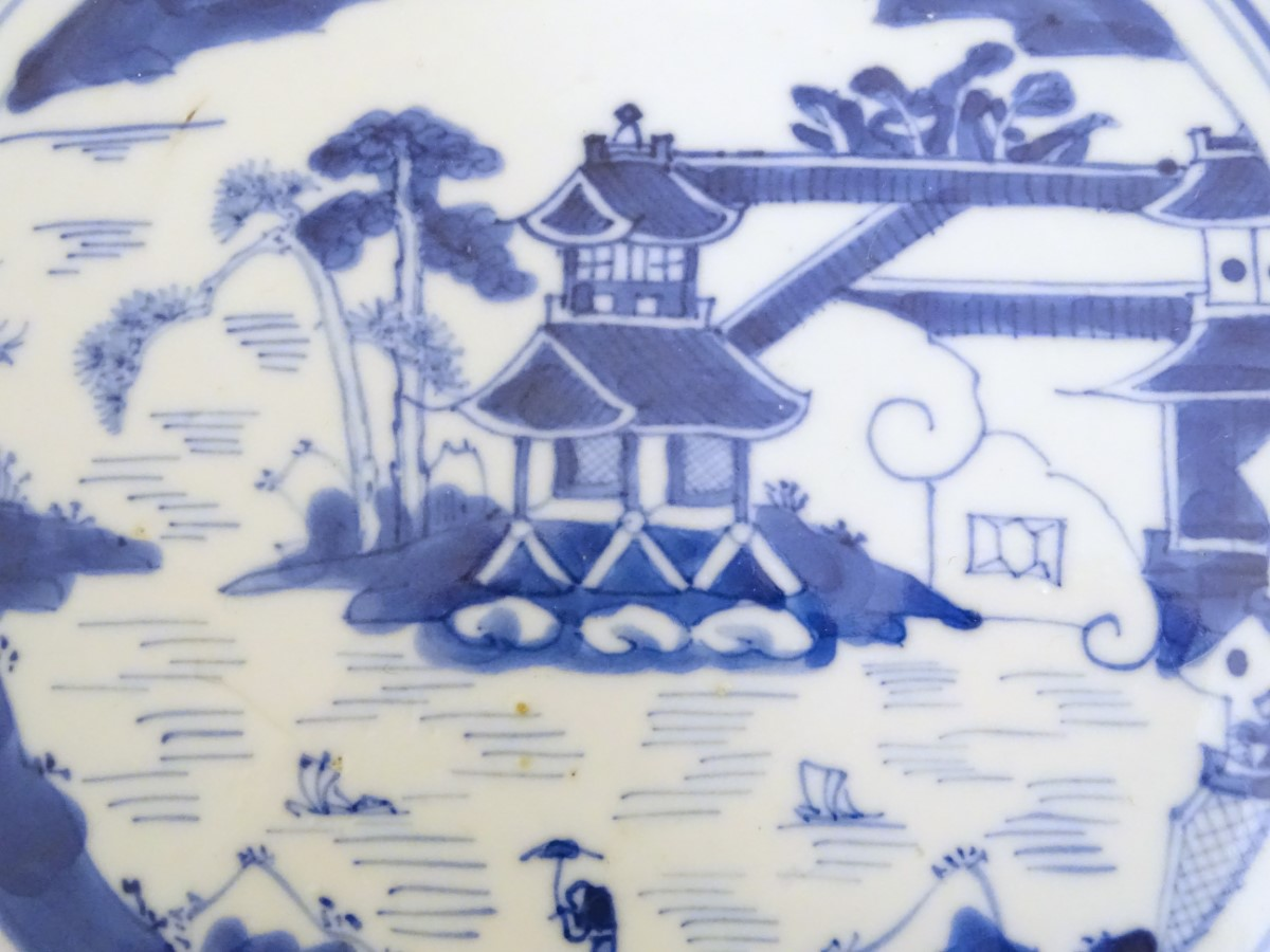 Lot 14 - A Chinese blue and white plate with hand painted decoration depicting a pagoda on an island,