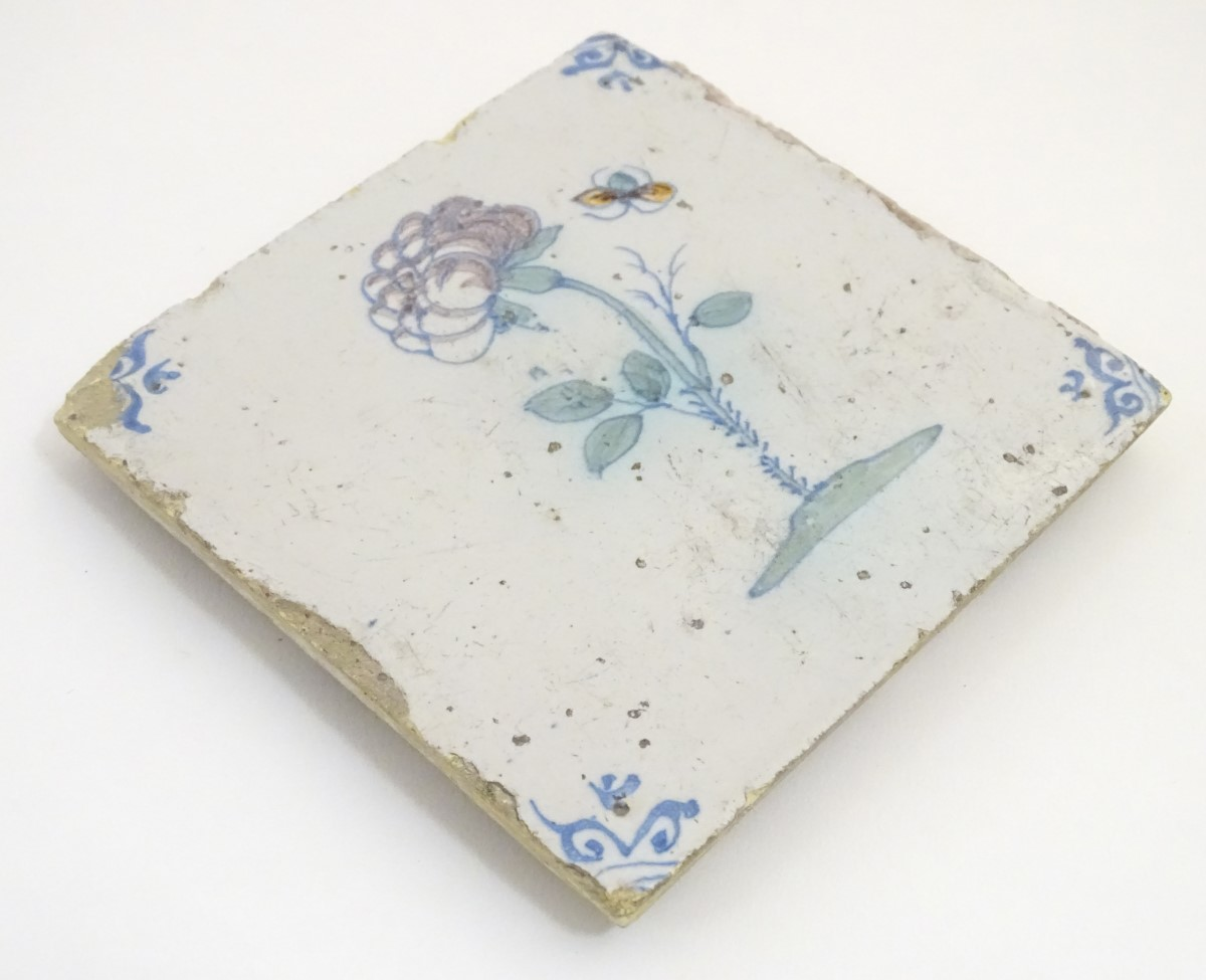 Lot 52 - A 17thC Delft tile depicting a flower and a flying insect, with blue ox-head corner motifs. Approx.