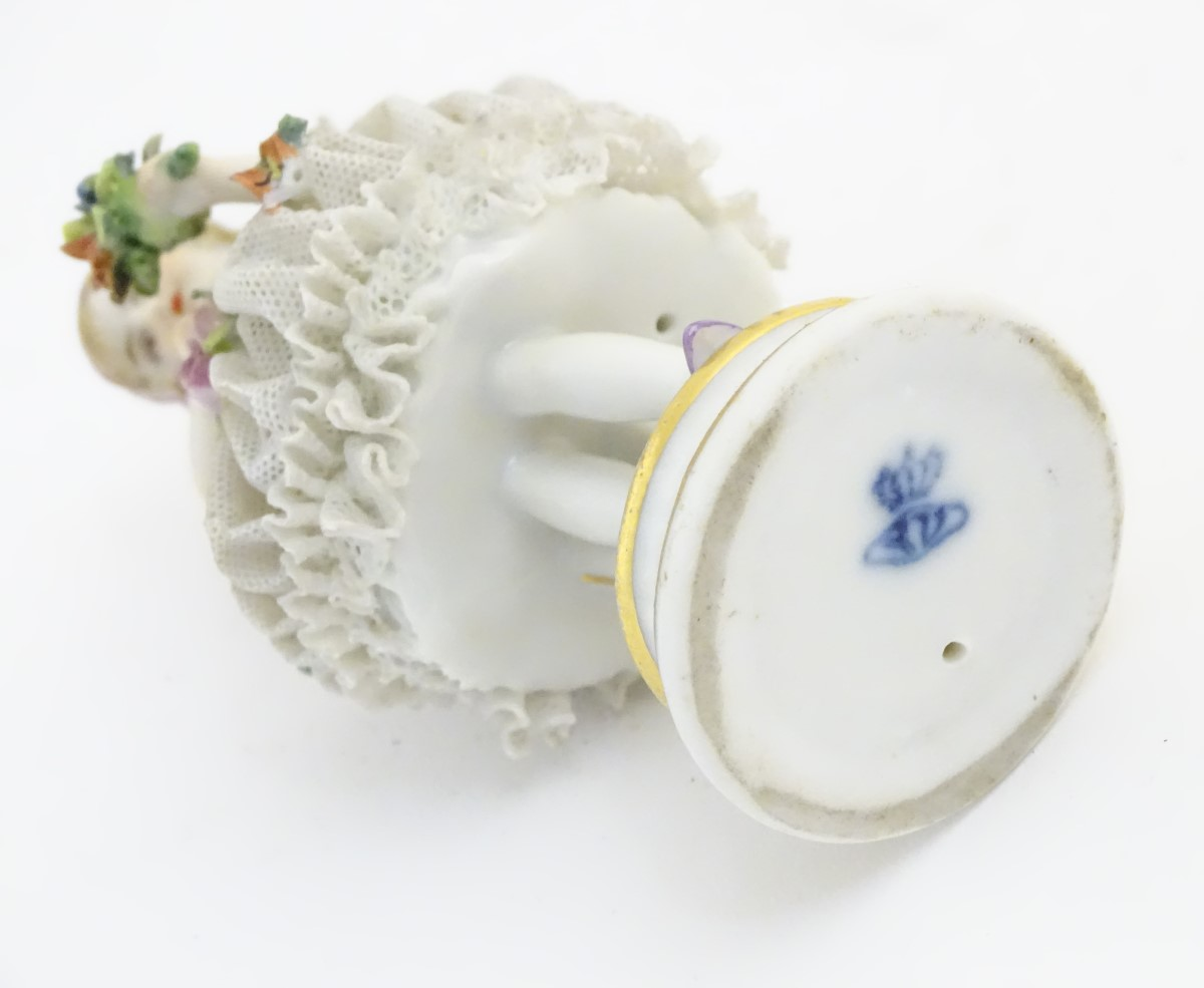 Lot 45 - A German porcelain figure of a flower girl with a porcelain lace skirt on a circular base with gilt