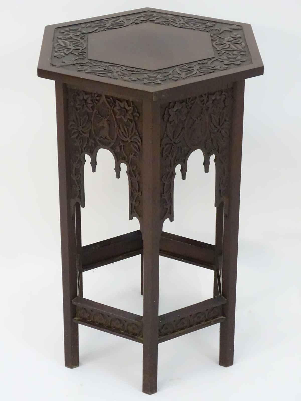 Lot 822 - A walnut Liberty style table with a hexagonal carved top above six matching carved facades with