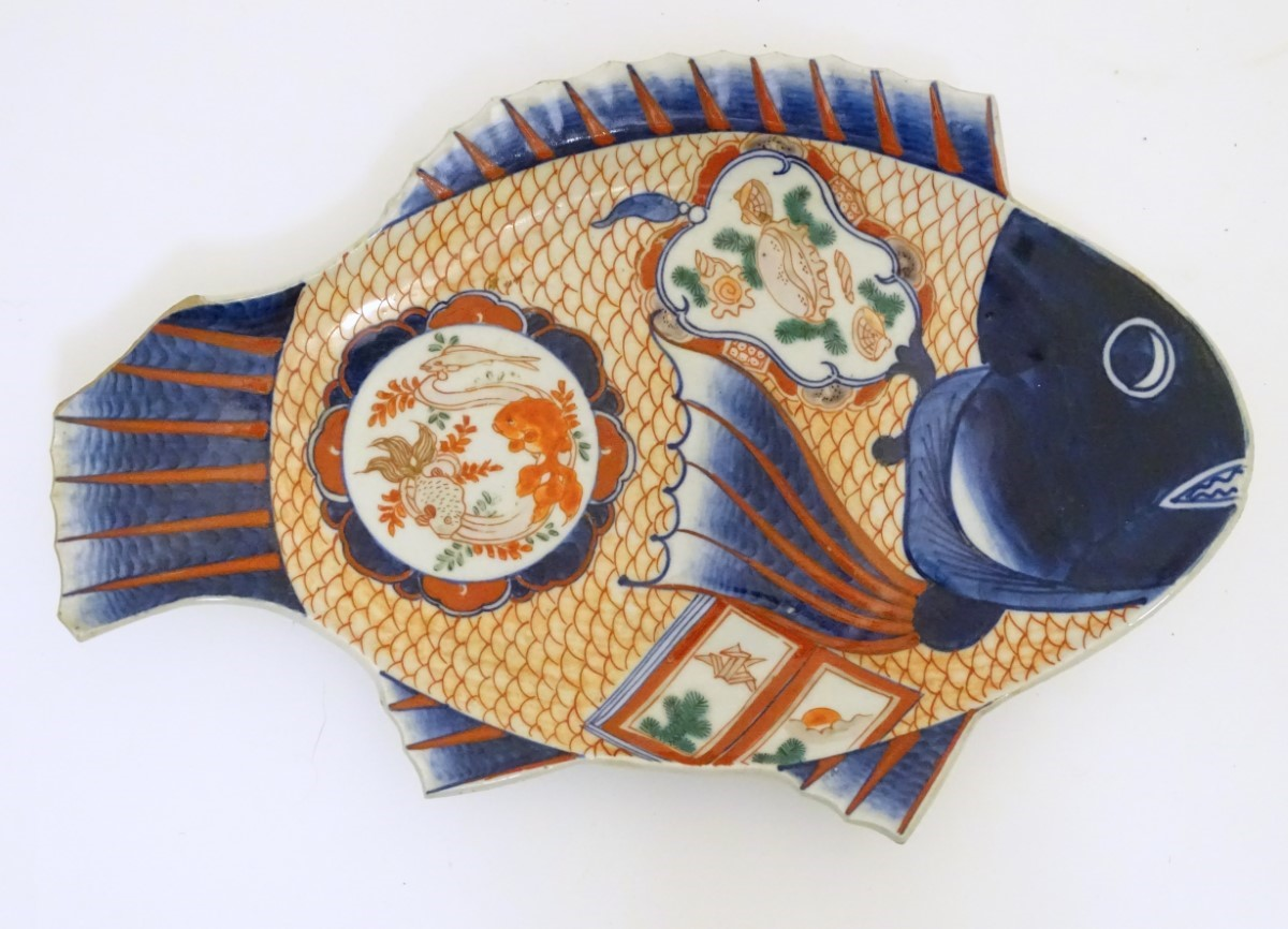 Lot 18 - An Imari dish formed as a fish, decorated with panels depicting shells and fish,