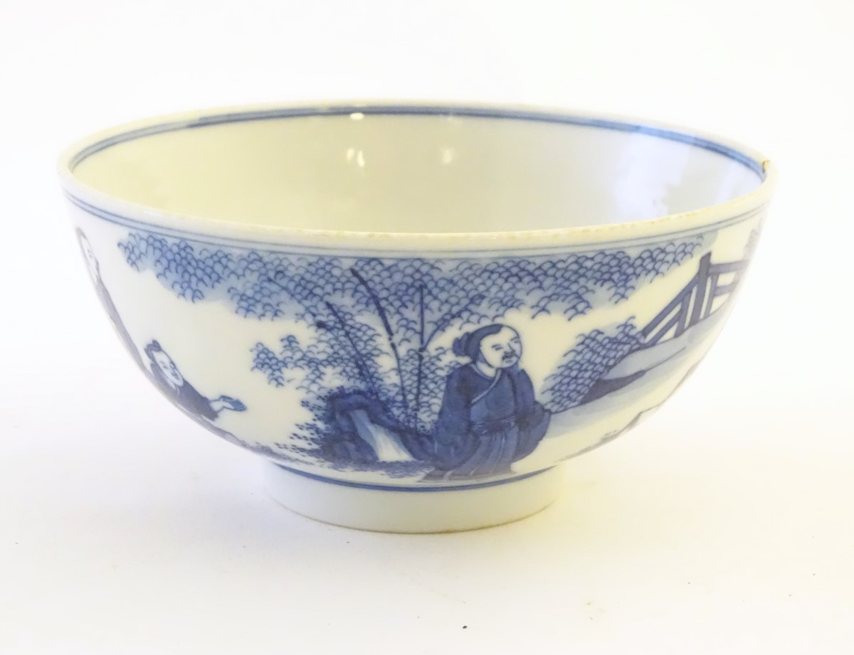 Lot 23 - A Chinese blue and white bowl depicting scenes of figures in landscapes,