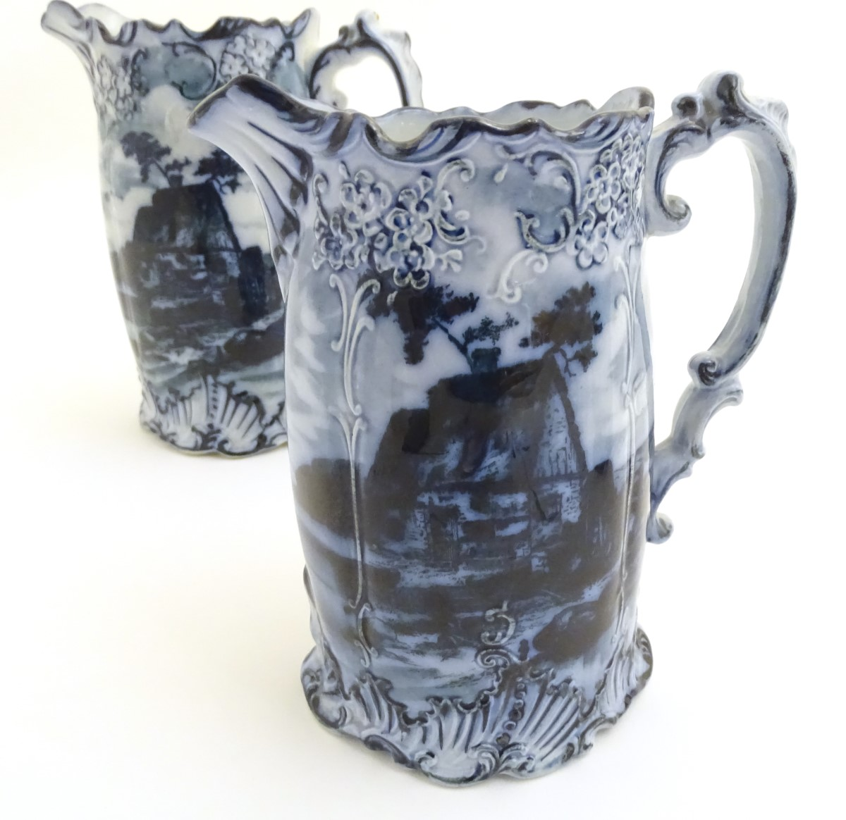 Lot 36 - Three Victorian blue and white graduated jugs with transfer decoration depicting landscapes with