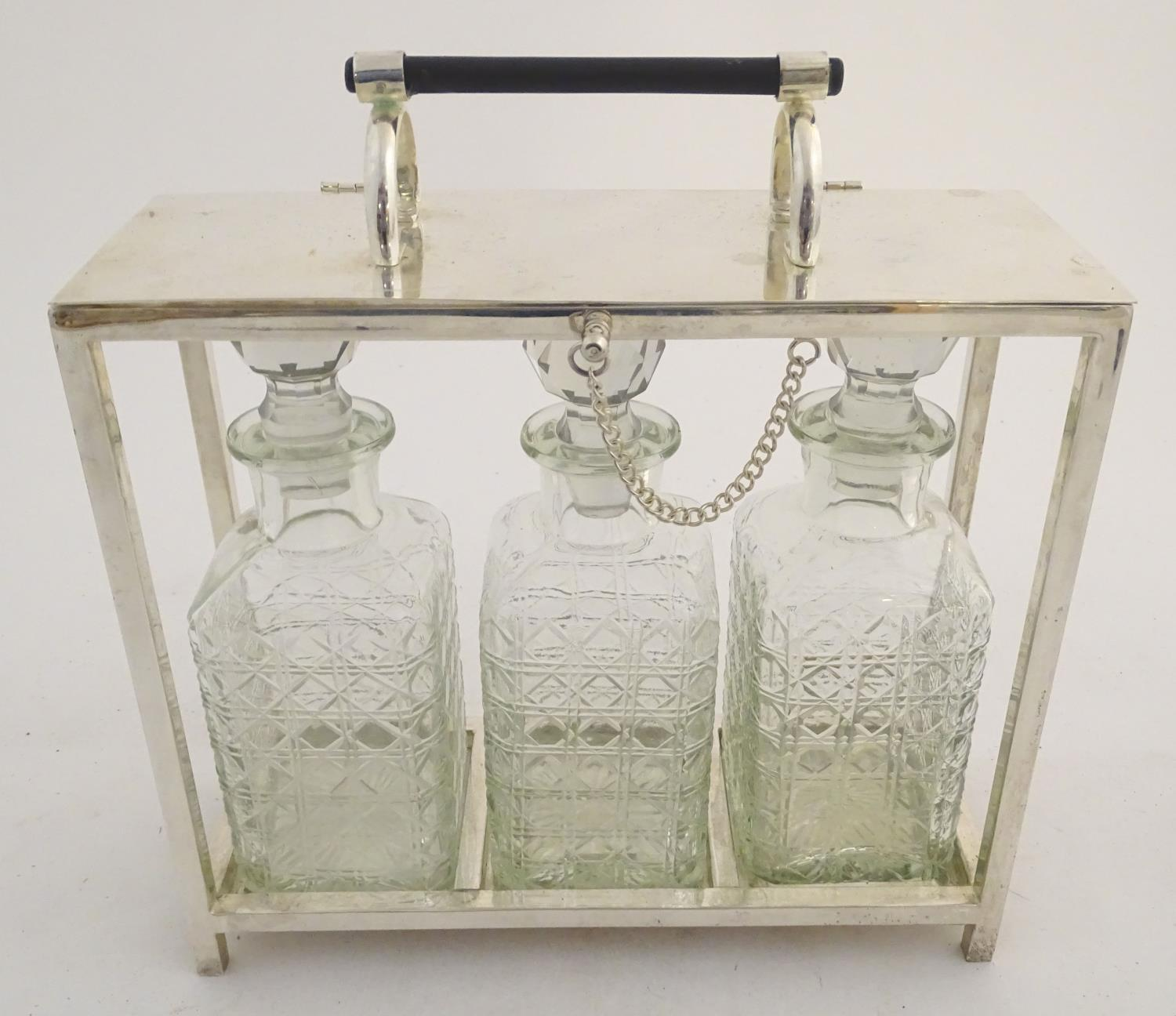 "Lot 886 - A Dr Christopher Dresser style tantalus with provision for three decanters. Approx. 11 1/2"" high"