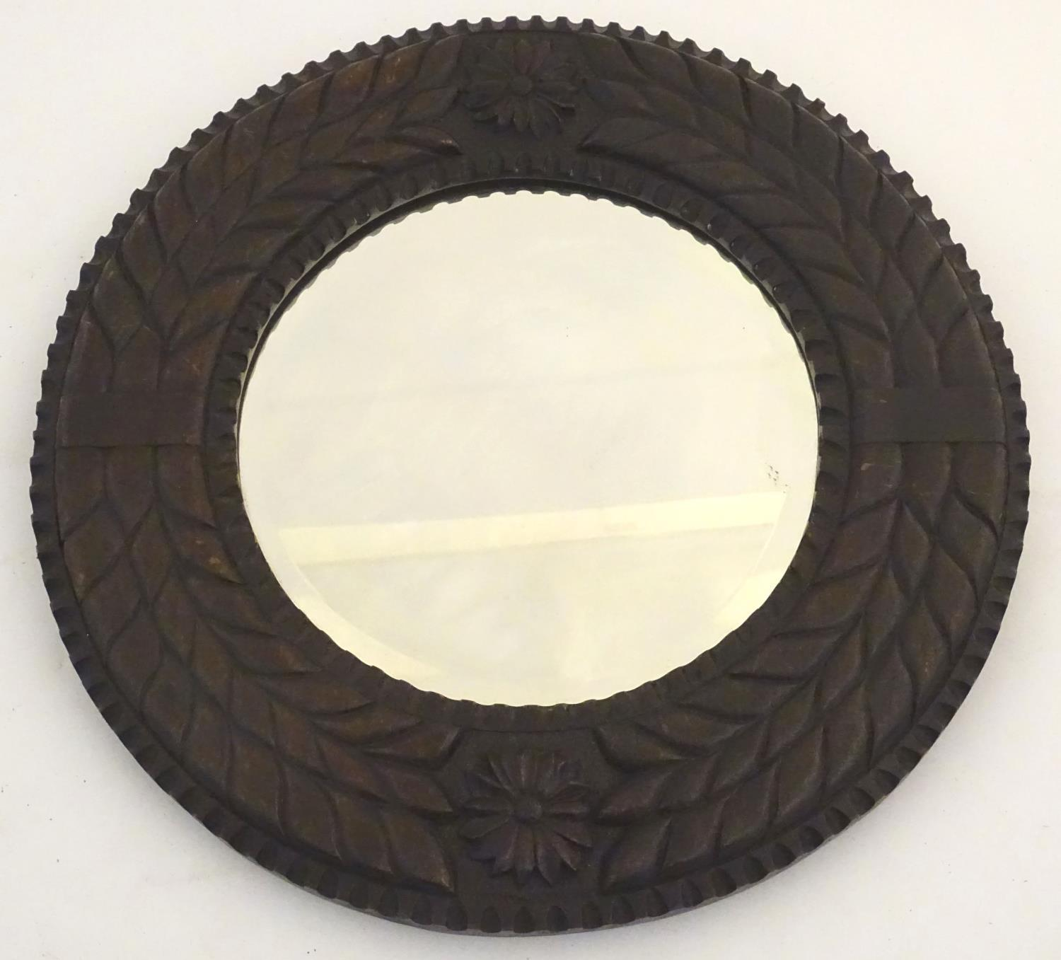 Lot 888 - A late 19th / early 20thC circular mirror with bevelled glass within a carved mahogany frame with