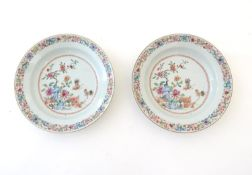 A pair of Chinese dishes decorated with a garden / terrace scene with flowers and foliate with two