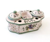 A Continental faience standish with two lidded inkwells and floral and foliate detail. Approx. 3 1/