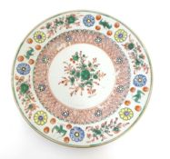 A Chinese plate with central floral and foliate detail, with a patterned border with flowers and