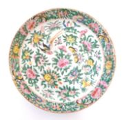 A Chinese Cantonese plate / dish decorated with birds, butterflies, flowers and foliage. Approx. 9