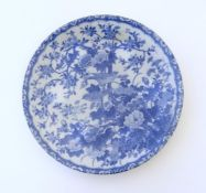 An Oriental blue and white plate with floral and foliate detail with birds on branches. The