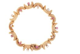 A 1960'S TIFFANY & CO CRESCENT MOON BRACELET SET WITH RUBIES AND DIAMONDS IN 18CT YELLOW GOLD