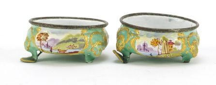 Pair of 19th century French enamel salts, hand painted with panels of farm and landscape scenes, 7cm