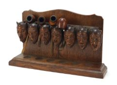 Carved oak devil head design pipe stand with four pipes including two with silver mounts, the rack