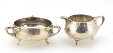Northern Goldsmith Company, Arts & Crafts planished silver milk jug and sugar bowl, London 1901, the