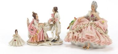 Dresden, three German porcelain lace figurines including a group of two lovers, the largest 18cm