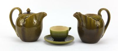 Linthorpe, two Arts & Crafts pottery jugs and a cup with saucer having green glazes in the manner of
