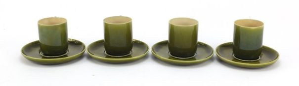 Four Linthorpe Arts & Crafts pottery coffee cans and saucers having green glazes in the manner of