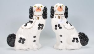 A pair of early 20th Century ceramic Wood and Sons Staffordshire fire dogs having hand painted black