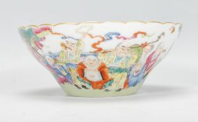 A 20th Century Chinese famille rose porcelain bowl being hand painted with immortals, depicting 18