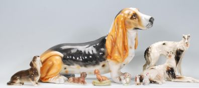 A collection of ceramic dog figurines to include a basset hound, two lurcher figurines marked RS,