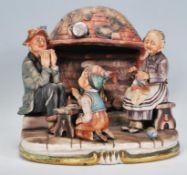 A 20th century Capodimonte of Naples ceramic group ornament entitled 'fireside' depicting a family