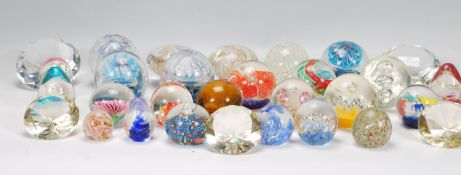 A large collection of approximately 30 20th Century paper weights to include some diamond shaped