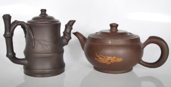 A pair of 20th century Chinese Yi Xing terracotta teapots. One of the teapots has a bamboo design on