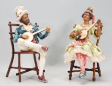 A pair of 20th Century ceramic continental creole band figures seated upon bamboo chairs playing