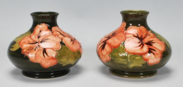 Walter Moorcroft - A pair of Moorcroft tubelined Hibiscus pattern vases of squat globular form