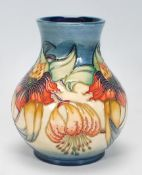A Moorcroft vase of globular form in theAnna Lilly pattern. Tubelined on a blue and cream ground.