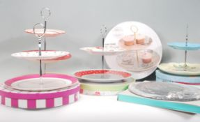A group of six contemporary china cake stands to include a Rosies Pantry two tier cake stand, two