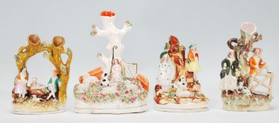 A group of four 19th Century Victorian Staffordshire spill / tulip vases each adorned with figures