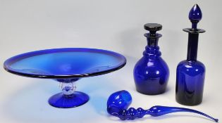 A group of Bristol blue glassware to include two decanters one of bell shaped form and the other