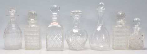 A group of seven vintage and antique cut glass decanters to include a pair of whiskey decanters with