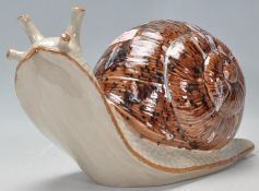 A vintage late 20th Century studio art pottery figurine in the form of a snail having a mottled