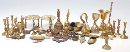 A good collection of miniature brass candlestick, brass trivets with pierced top, brass table bells,