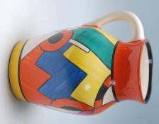 A Wedgwood Bizarre by Clarice Cliff Blue 'W' jug being hand painted with geometric decoration to the