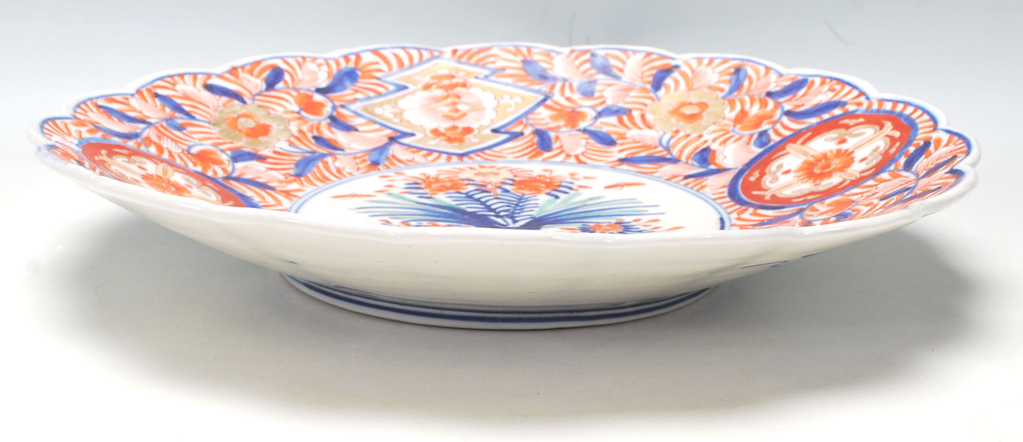 Lot 46 - A 19th Century Japanese Imari charger plate with scalloped rim, typical decoration with a vase of
