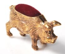 A brass cased pincushion in the form of a pot bellied pig with red velvet cushion to the back.