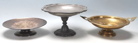 A collection of three tazza dishes, comprising of a tall pewter example with floral decoration to