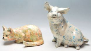 Two 20th Century ceramic large figurines in the form of a pig and a crouching cat each having
