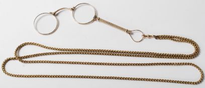 A pair of early 20th Century yellow metal lorgnettes / spectacles opera glasses having an extendable
