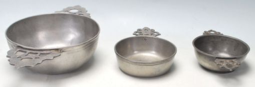 A collection of three early 20th Century pewter porringer / drinking bowls having pierced twin