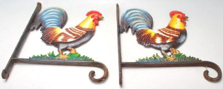 A pair of vintage 20th century cast iron cockerel / rooster wall mounted flowerbasketbrackets.